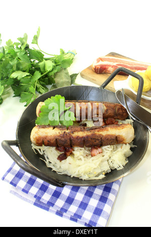 a pan with sourcrout and fried sausage - Stock Photo