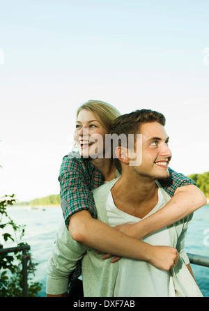 Young Man giving Young Woman Piggyback Ride, Mannheim, Baden-Wurttermberg, Germany - Stock Photo