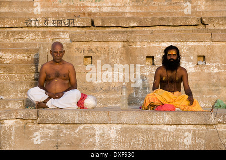 Hindu devotions at the Ghats on the Holy River Ganges in Varanasi in the Uttar Pradesh region of northern India - Stock Photo