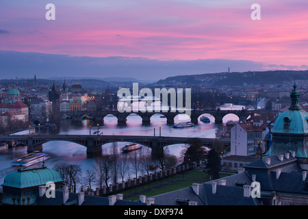 the Manes, Charles and Legion Bridges over the Vltava River at dusk, with the Old Town on the left, Prague, Czech - Stock Photo