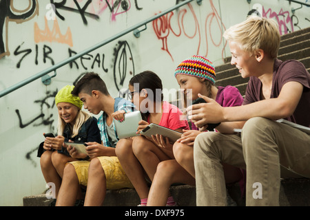 Group of children sitting on stairs outdoors, using tablet computers and smartphones, Germany