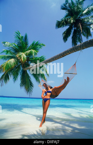 Couple on island holidays relaxing in hammock on sandy beach in paradise - Stock Photo