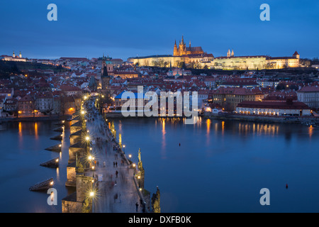 the Charles Bridge over the Vltava River at dusk with the Castle District and St Vitus's Cathedral beyond Prague Czech Republic