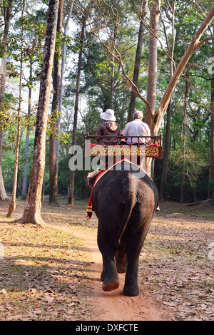 Tourists on an Elephant ride in Siem Reap around the ruined temples of Cambodia's famed Angkor Wat - Stock Photo