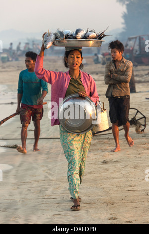 Burmese woman with her catch of fish, near the fishing village on Ngapali Beach in Myanmar (Burma). - Stock Photo