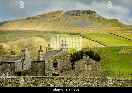 Pen-y-Ghent one of the Yorkshire Three Peaks looms over houses at Horton-in-Ribblesdale in the Yorkshire Dales National - Stock Photo
