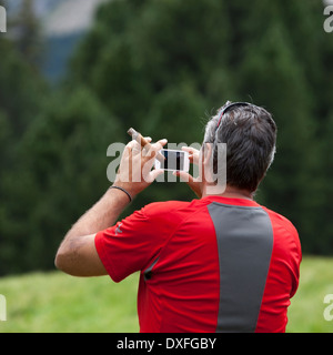 Photographer with iPhone and cigar - Stock Photo