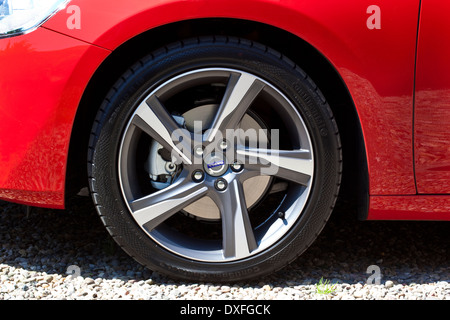 The front wheel of a new red Volvo S60 sports saloon car. - Stock Photo