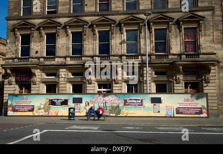 Derby England UK. a couple sitting on a bench with a hoarding behind them advertising the opening of LOLA LO a new - Stock Photo