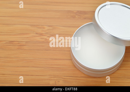 Pure shea butter in metallic tin on wooden background. Perfect lip balm and beauty balm. Plenty of copy space. - Stock Photo