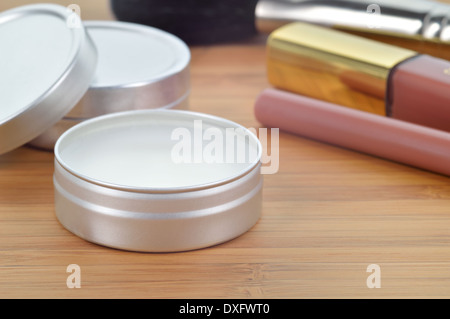Pure shea butter in metallic tin on a wooden background. Perfect lip balm and beauty balm against of other lip cosmetics. - Stock Photo