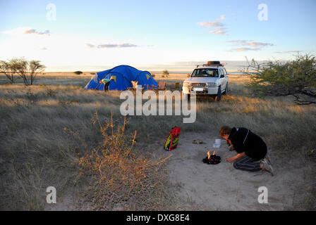 Lighting a campfire, and camping at the edge of the flooded Sowa Pan in the Makgadikgadi Pans, Botswana. - Stock Photo