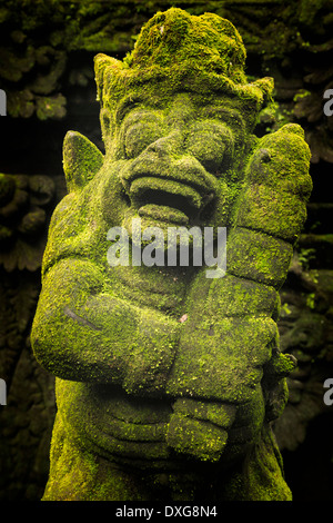 Moss covered statue of a guard in the Pura Luhur Batukau complex, central Bali, Indonesia. - Stock Photo