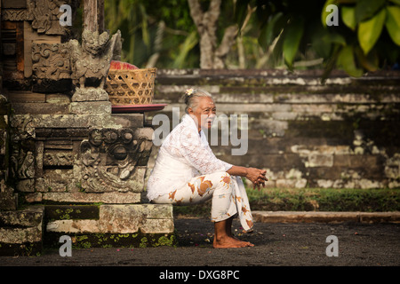 Woman resting on the steps of the Pura Taman Ayun, part of the Mengwi Hindu temple complex in Badung, Bali, Indonesia. - Stock Photo
