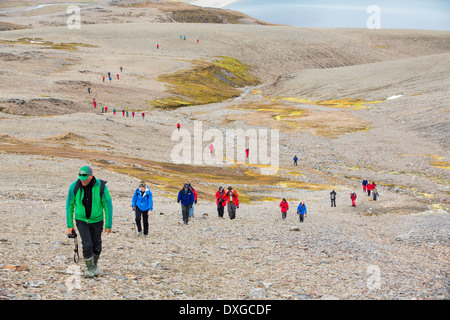 Passengers on an expedition cruise to Anarctica recreat part of Shakleton's famous walk across South Georgia. - Stock Photo
