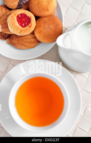 a cup with tea and some biscuits in a plate, on a set table - Stock Photo
