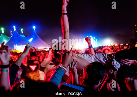 Man crowd surfing at music festival - Stock Photo