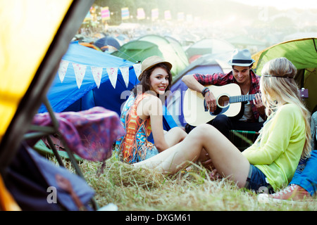 Friends with guitar hanging out near tents at music festival - Stock Photo