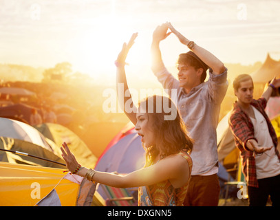Friends dancing outside tents at music festival - Stock Photo