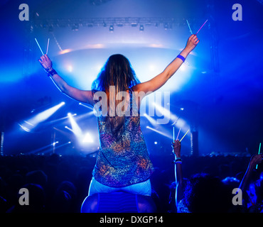 Cheering woman with glow sticks on manÍs shoulders at music festival - Stock Photo