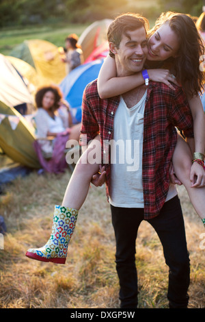 Man piggybacking woman outside tents at music festival - Stock Photo