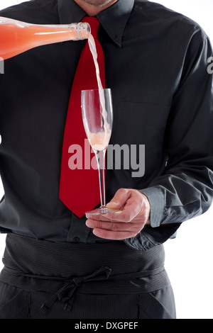 Bartender pouring cocktail in glass - Stock Photo