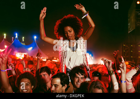 Cheering woman on manÍs shoulders at music festival - Stock Photo