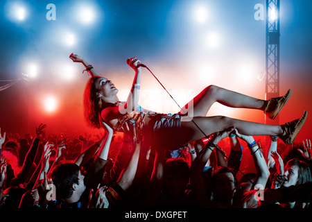 Performer crowd surfing at music festival - Stock Photo