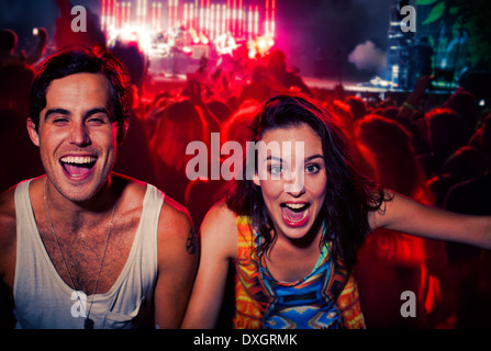 Enthusiastic couple cheering at music festival - Stock Photo