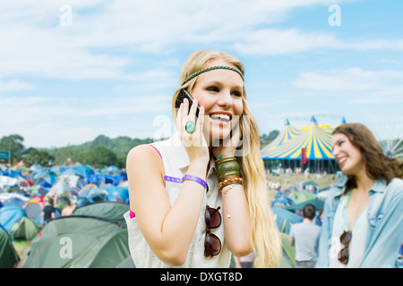 Woman talking on cell phone outside tents at music festival - Stock Photo