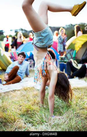 Woman doing handstand outside tents at music festival - Stock Photo