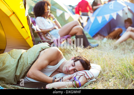 Man sleeping in sleeping bag outside tent at music festival - Stock Photo