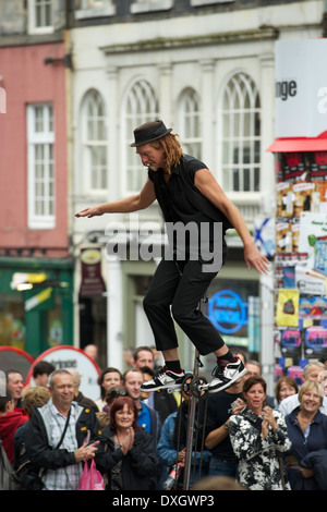 Unicyclist entertains the crowds on the Royal Mile. - Stock Photo