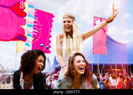 Woman piggybacking enthusiastic friend at music festival - Stock Photo