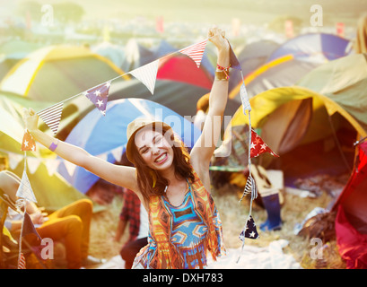 Portrait of enthusiastic woman outside tents at music festival - Stock Photo