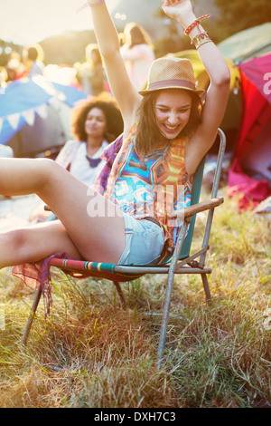 Enthusiastic woman in lawn chair outside tents at music festival - Stock Photo