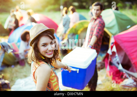 Portrait of woman helping man carry cooler outside tents at music festival - Stock Photo