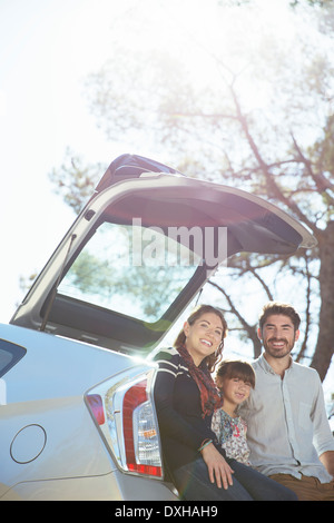Portrait of smiling family sitting against rear of car - Stock Photo