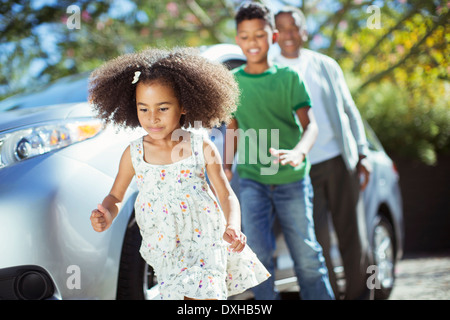 Family running outside car - Stock Photo