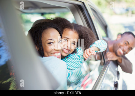 Portrait of happy family leaning out car windows - Stock Photo