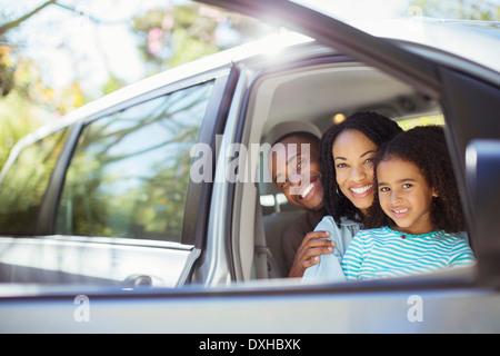 Portrait of happy family inside car - Stock Photo