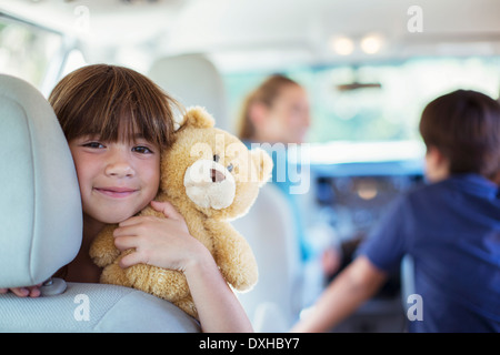 Portrait of happy girl with teddy bear in back seat of car - Stock Photo