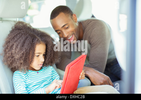 Father and daughter using digital tablet in back seat of car - Stock Photo