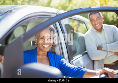 Portrait of happy senior couple inside and outside of car - Stock Photo