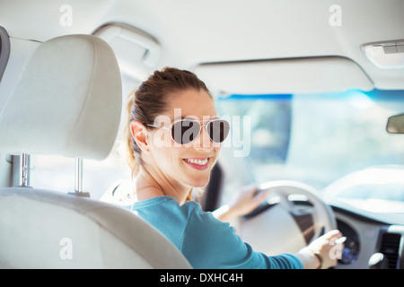 Portrait of confident woman in sunglasses driving car - Stock Photo