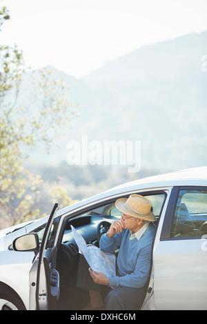 Senior man checking map in car - Stock Photo