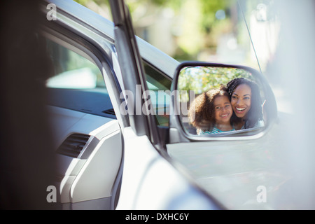Reflection of smiling mother and daughter in side-view mirror