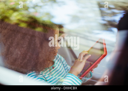 Girl using digital tablet in back seat of car - Stock Photo