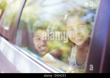 Portrait of happy brother and sister looking out car window - Stock Photo