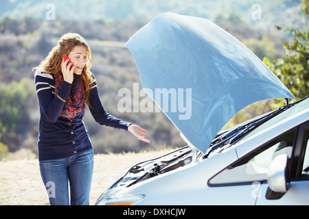 Frustrated woman talking on cell phone with automobile hood raised at roadside - Stock Photo